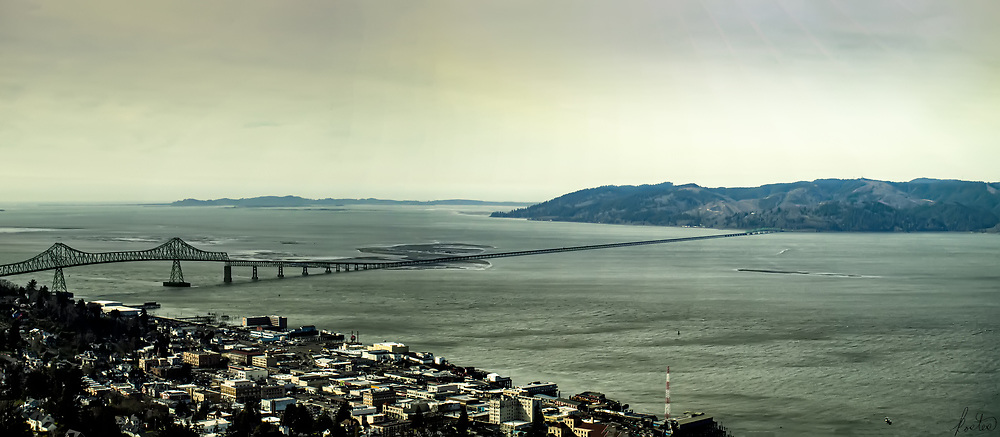A panorama of Astoria, Oregon on a cloudy day, with a bit of sun breaking through.
