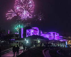 Edinburgh's Hogmanay celebrations start with the traditional torchlit procession. This year the route finishes outside the Scottish Parliament in  Holyrood where a word chosen by the young people of Scotland that makes them proud to live in the country is revealed by the thousands of torch bearers.<br /> <br /> Pictured: Fireworks over the Scottish Parliament