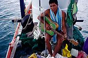 A Thai fisherman on the island of Koh Samui plays his guitar