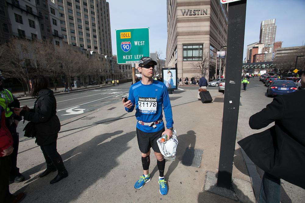 Boston, MA 04/15/2013.Boston Marathon runner Bernard Spielhagen checks his phone as he evacuates Copley Plaza after two explosions on Monday..Alex Jones / www.alexjonesphoto.com