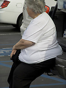 overweight woman sitting in on the back of a car while waiting