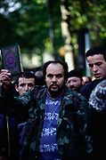 A man hold a Koran as Muslim protesters demonstrate against Israel and the West outside the Regents Park Mosque.