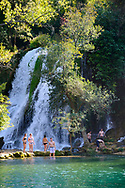 Backpackers from several countries, traveling in Europe, enjoy the stunning scenery and cool water at Kravice Waterfalls in Bosnia and Herzegovina