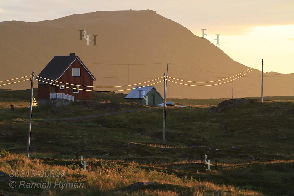 Golden light of sunset washes across farmhouse and tallest mountain on Ingoya island, Finnmark, Norway.