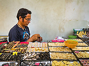 27 NOVEMBER 2015 - BANGKOK, THAILAND: A street vendor puts together an amulet in his market stall. Hundreds of vendors sell amulet and Buddhist religious paraphernalia to people in the Amulet Market, a popular tourist attraction along Maharat Road north of the Grand Palace near Wat Maharat in Bangkok. Bangkok municipal officials announced that they are closing the market and forcing vendors to relocate to an area about one hour outside of Bangkok. The closing of the amulet market is the latest in a series of municipal efforts to close and evict street vendors and markets from areas that have potential for redevelopment. The street vendors will be evicted from the area by Sunday, Nov. 29.    PHOTO BY JACK KURTZ