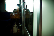 TOKYO, JAPAN, 11 JULY - Keisei line - A young woman in the train use her mobile.  A strong light from outside erase a part of her face that can not permit us to know her identity - 2012