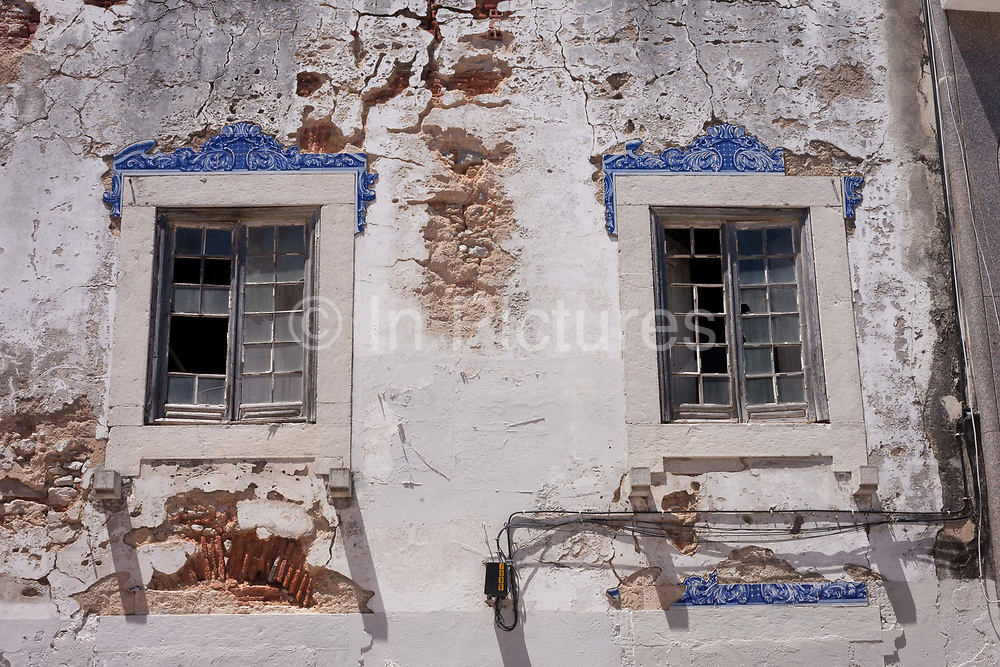 A detail of broken windows, crumbling plaster and brickwork, of a derelict, abandoned house that features traditional Portuguese tiles, on 12th July 2016, at Cascais, near Lisbon, Portugal. Across the country, and even at important tourist landmarks, buildings sit vacant and often collapsing. Sometimes it is because a previous generation have passed away to leave properties in the hands of arguing families. Beautiful buildings are therefore left to collapse in town centres.