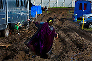 Man in costume trying to negociate a muddy field in the in the Shangri La camping field, after heavy rain, Glastonbury Festival 2016, United Kingdom. Glastonbury Festival is the largest greenfield festival in the world, and is now attended by around 175,000 people. Its a five-day music festival that takes place near Pilton, Somerset. In addition to contemporary music, the festival hosts dance, comedy, theatre, circus, cabaret, and other arts. Held at Worthy Farm in Pilton, leading pop and rock artists have headlined, alongside thousands of others appearing on smaller stages and performance areas.