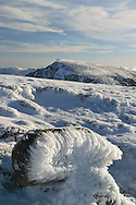 Aonach Beag from Aonach Mor in winter with foreground boulder covered in hoar frost