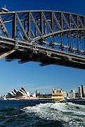 Ferry sailing beneath Sydney Harbour Bridge, with Sydney Opera House in background. Sydney, Australia