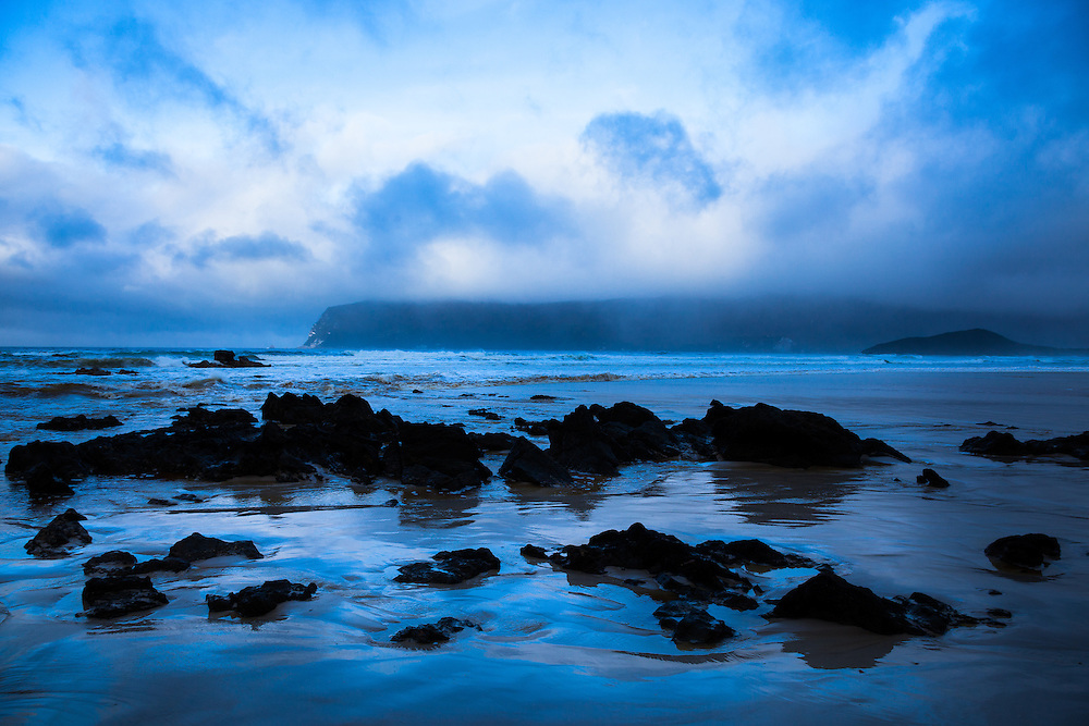 Clouds cloak the mountains and beach around Cox Bight in Southwest National Park. Tasmania.