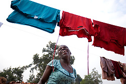 Phiona Mutesi, a 14-year-old chess prodigy, hangs clothes to dry inside Katwe, the largest slum in Kampala, Uganda, Dec. 10, 2010. Mutesi lives in the slums of Uganda and is just now learning to read. But her instincts have made her a player to watch in international chess. Mutesi, a naturally talented chess player is coached by Robert Katende of Sports Outreach Ministry. The chess club meets at the Agape Church.
