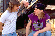Rock musicians age 19 talking by railroad bridge.  St Paul Minnesota USA