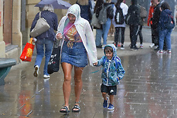 © Licensed to London News Pictures. 28/07/2021. Sheffield, UK. Members of the public brave the rain in Sheffield as parts of Yorkshire are hit by heavy rain and thunderstorms. Photo credit: Ioannis Alexopoulos/LNP
