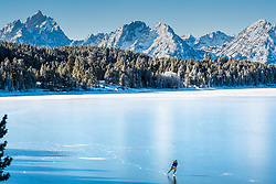 Ice skater on Jackson Lake in Grand Teton National Park. It is a rare time when this lake isn't covered with snow before the ice is thick enough for skating.