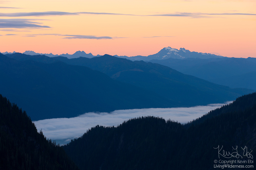 A blanket of fog covers Baker Lake, located in the North Cascades of Washington state. Several peaks that are part of North Cascades National Park are visible on the horizon, including Bacon Peak at right.
