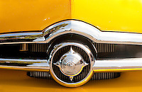 Shining chrome grill work on yellow hood - 1950 Ford Coupe