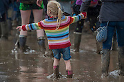 A young girl tries to lead her mother further in - A large puddle left over from teh previous nights rain addsto the problems of moving around  albeit some see it as a leisure facility- 2016 Glastonbury Festival, Worthy Farm, Glastonbury.