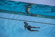 """London, United Kingdom, Jun 3, 2021: A swimmer is seen swimming in a 25-metre sky pool in Embassy Gardens linking two residential buildings in London's Nine Elms, floating 10 storeys above ground on Thursday, Jun 3, 2021. The Sky Pool, described as """"the world's first floating pool"""", is only open to some of the development's residents, where rent is from about £1,800 to £6,500 per month. (Photo by Vudi Xhymshiti)"""