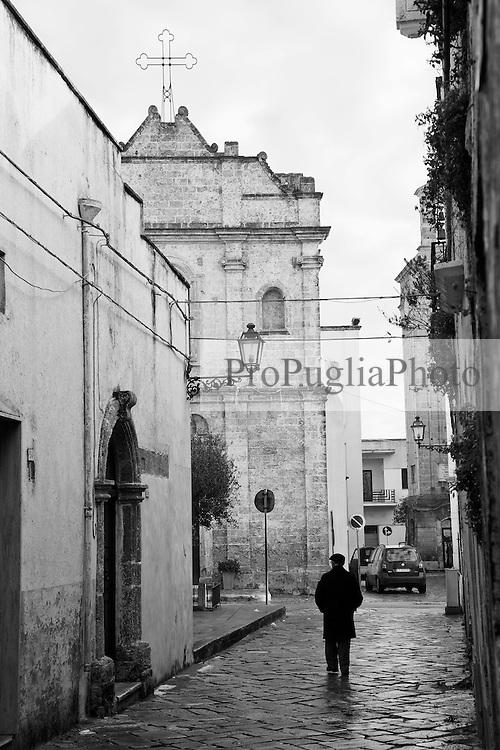 Persona anziana nel centro storico di Racale (LE) che si avvia verso la chiesa.