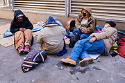 """16 FEBRUARY 2021 - DES MOINES, IOWA: A group of homeless people camp next to building exhaust grates in an alley in downtown Des Moines Tuesday. The grates put out heated air. Iowa, like much of the United States, is in the grip of a frigid Polar Vortex. Temperatures in Iowa have been 30F below normal for more than a week. Tuesday morning, 15 February, was the coldest morning so far and is expected to be the coldest morning in central Iowa this winter. The temperature in Des Moines was -17F (-27C), with the windchill factored in the """"feels like"""" temperature was -25F  (-32C). Schools have been closed for the last two days so students wouldn't have to stand outside waiting for buses. Most outdoor activities, like outdoor construction and road work, are paused until temperatures rebound. The public libraries, closed because of the Coronavirus pandemic, were opened as warming centers, and the city buses were free so people could ride the buses to stay warm.      PHOTO BY JACK KURTZ"""