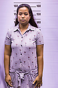 "17 JULY 2014 - BANGKOK, THAILAND: An undocumented Cambodian woman stands up for her ""mug shot"" for a temporary ID card at the temporary ""one stop service center"" in the Bangkok Youth Center in central Bangkok. Thai immigration officials have opened several temporary ""one stop service centers"" in Bangkok to register undocumented immigrants and issue them temporary ID cards and work permits. The temporary centers will be open until August 14.    PHOTO BY JACK KURTZ"