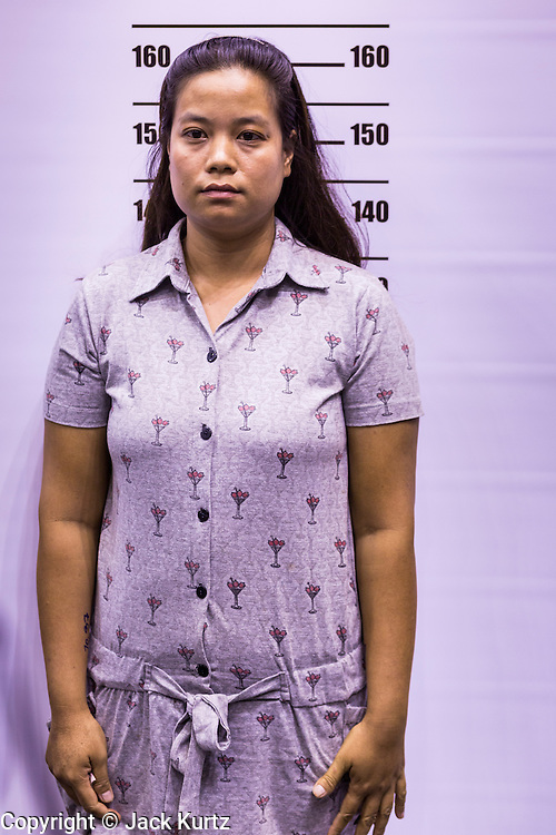 """17 JULY 2014 - BANGKOK, THAILAND: An undocumented Cambodian woman stands up for her """"mug shot"""" for a temporary ID card at the temporary """"one stop service center"""" in the Bangkok Youth Center in central Bangkok. Thai immigration officials have opened several temporary """"one stop service centers"""" in Bangkok to register undocumented immigrants and issue them temporary ID cards and work permits. The temporary centers will be open until August 14.    PHOTO BY JACK KURTZ"""