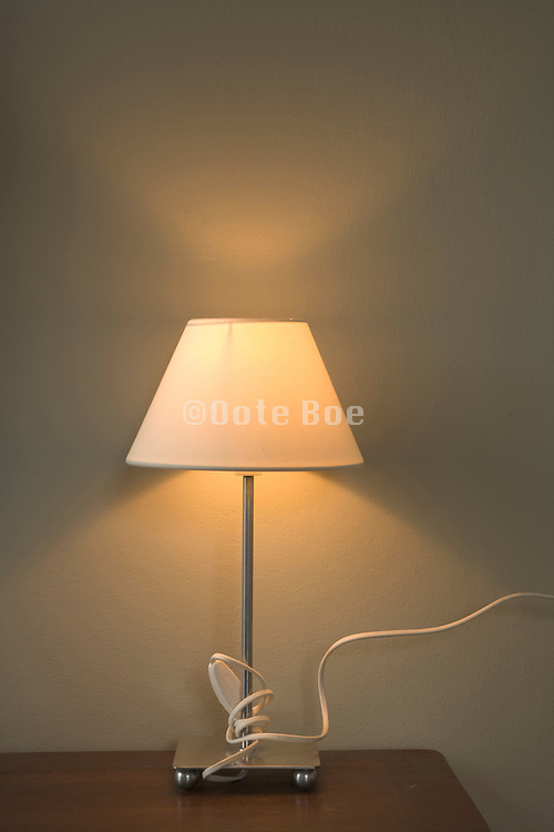 still life with a modern desk lampshade against a plain wall