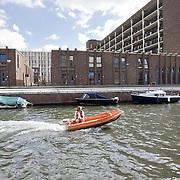 Nederland Amsterdam 15-09-2010 20100915..Nieuwbouw wijk IJburg, woningen in het hogere segment. Jongeman vaart in motorbootje door de wijk, langs de nieuwbouwwoningen en de boten die aan de kade liggen. IJburg is een woonwijk in aanbouw in het oosten van de gemeente Amsterdam, in de Nederlandse provincie Noord-Holland. Kenmerkend aan de in het IJmeer gelegen wijk is dat deze op kunstmatige eilanden is gebouwd. IJburg maakt onderdeel uit van het stadsdeel Oost. Holland, The Netherlands, dutch, Pays Bas, Europe , Yburg, het Ij, Het Y, , waterstand, watersysteem, waterveiligheid, waterveiligheid en gebiedsontwikkeling, waterwijk, waterwijken, waterwoning, waterwoningen, wijk, wijken, wonen aan het water, woning, woningaanbod, woningbouw, woningen, woningmarkt, woningvoorraad, woonbuurt, woonbuurten, woonlast, woonlasten, woonwijk, woonwijken ..Foto: David Rozing