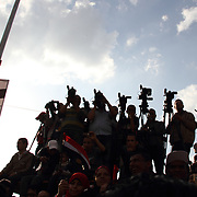 A silhouetted band of photographers and journalists focus on the platform of speakers leading the rally in Cairo's Tahrir Square during the Day of Justice and Cleansing.