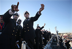 June 7, 2017 - AZ, USA - Chief Harrison Moorer, left, and Ahnas Akande, center, try to see where Senior Chief Herb Banks is pointing out his family on the dock in San Diego, CA. on Nov. 23, 2015 . The USS Theodore Roosevelt arrived in San Diego Monday morning at Naval Air Station North Island after an eight and a half month deployment to the U.S. fifth, sixth and seventh fleet areas of operation. The aircraft's arrival is San Diego is part of the three carrier shift involving the USS Ronald Reagan and USS George Washington. The nuclear flattop is transferring here after a 29-year career on the East Coast. (Credit Image: © Peggy Peattie/TNS via ZUMA Wire)