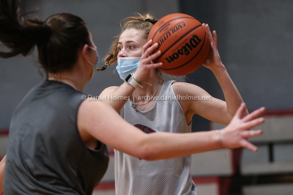 Millis High senior Abby Miller looks for an open teammate  during girls varsity basketball practice at Millis High School on Jan. 02, 2021.