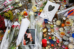 © Licensed to London News Pictures. 16/11/2015. Paris, France. Victims pictures left at memorial outside Bataclan Cafe in Paris, France following the Paris terror attacks on Monday, 16 November 2015. Photo credit: Tolga Akmen/LNP