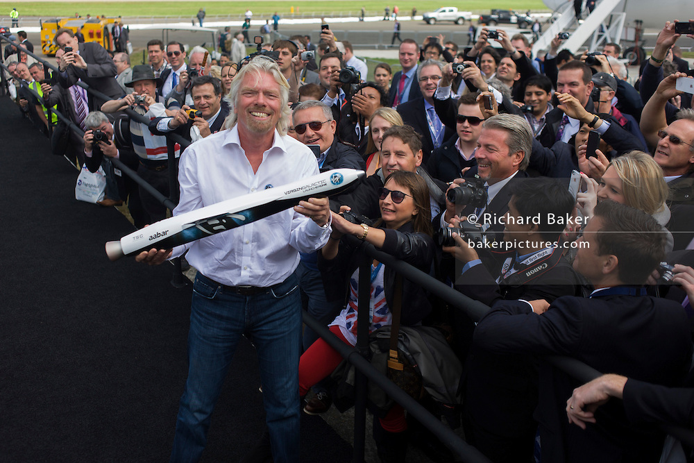 Richard Branson shows spectators a model of satellite LauncherOne after Virgin Galactic space tourism presentation at Farnborough