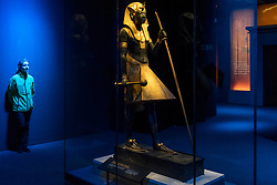 """© Licensed to London News Pictures. 01/11/2019. LONDON, UK. A staff member views """"Wooden Guardian Statue of the Ka of the King Wearing the Nemes Headcloth"""".  Preview of """"Tutankhamun, Treasures of the Golden Pharoah"""" at the Saatchi Gallery in Chelsea.  The exhibition celebrates the 100th year anniversary of the opening of Tutankhamun's tomb and displays 150 works in the largest collection of Tutankhamun's treasures ever to leave Egypt.  The show runs 2 November to 3 May 2020.  Photo credit: Stephen Chung/LNP"""