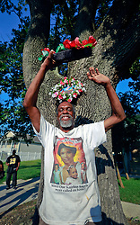 29 August 2013. Lower 9th Ward, New Orleans, Louisiana.<br /> Hurricane Katrina memorial 8 years later. <br /> Robert Green, activist and survivor of Hurricane Katrina holds a wreath and wears a t-shirt in memory of his mother and grand daughter who perished in the storm. Every year on the anniversary, Mr Green posts a wreath to the tree near where his loved ones succumbed to the storm.<br /> Photo; Charlie Varley
