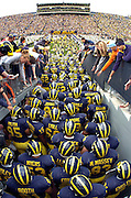 """The University of Michigan football team takes to the field at Michigan Stadium, """"The Big House"""", in  Ann Arbor, MI."""