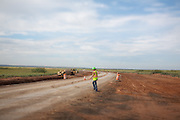 A construction worker walks across a highway under construction near The Waste Isolation Pilot Plant in Eddy County. WIPP received $172 million as part of the Recovery and Reinvestment Act. The highway will increase access for trucks carrying nuclear waste to the WIPP.