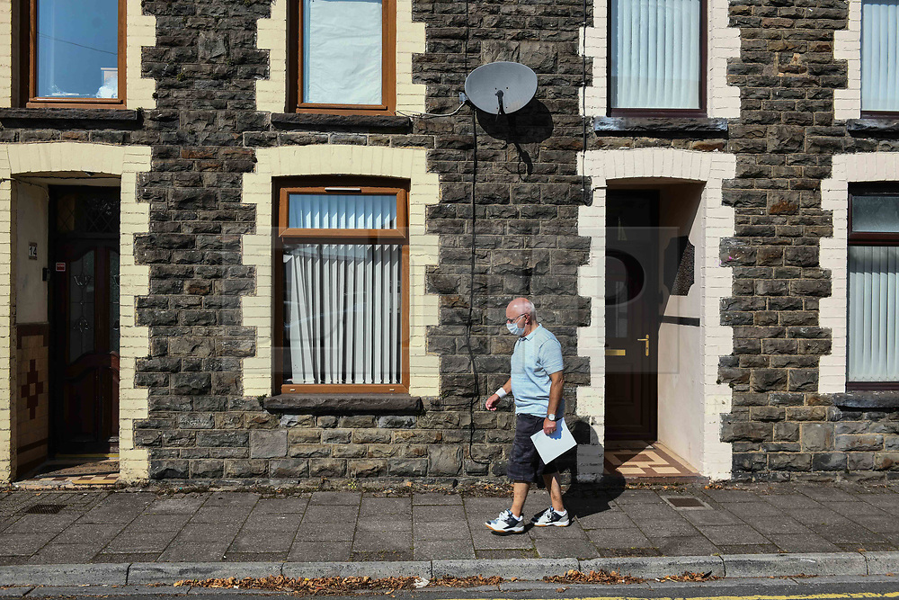 © Licensed to London News Pictures. 17/09/2020. Rhondda Valley, UK. A man wearing a mask walks along a traditional terraced street in the former mining town of Treorchy in the Rhondda Valley which will go into local lockdown today after a spike in the coronavirus infection rate in the borough of Rhondda Cynon Taff in south Wales.. Photo credit: Robert Melen/LNP