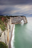 """A moody representation, with an incoming storm in the background, of the cliff known as La Manneporte, which is part of the amazing rocky coast around Etretat in Upper Normandy, France, altogether known as Les Failases d'Etretat..La Manneporte, which in French means """"the great door"""" is one of the most beloved subject of the famous French impressionist painter Claude Monet, who depicted it in more of 40 paints..Monet loved very much Etretat and its cliffs, and settled here his house and atelier for years."""