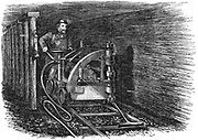 Rail mounted coal cutting machine powered by compressed air produced by a steam engine at the pithead. Wood engraving 1864