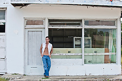 man-with-an-open-shirt-standing-in-front-of-a-run-down-garage