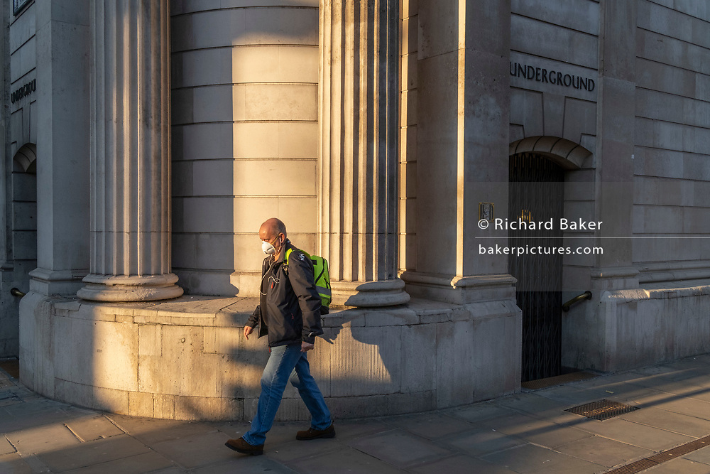 During the third lockdown of the Coronavirus pandemic, a man wearing a face covering walks past the closed entrance of Bank Underground Station on Threadneedle Street in the heart of the City of London, the capital's financial district, on 27th February 2021, in London, England.