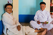 "29 MARCH 2012 - TAY NINH, VIETNAM:  Men who are members of the Cao Dai wait for noon prayer services to start at the Cao Dai Holy See in Tay Ninh, Vietnam. Cao Dai (also Caodaiism) is a syncretistic, monotheistic religion, officially established in the city of Tây Ninh, southern Vietnam in 1926. Cao means ""high"" and ""Dai"" means ""dais"" (as in a platform or altar raised above the surrounding level to give prominence to the person on it). Estimates of Cao Dai adherents in Vietnam vary, but most sources give two to three million, but there may be up to six million. An additional 30,000 Vietnamese exiles, in the United States, Europe, and Australia are Cao Dai followers. During the Vietnam's wars from 1945-1975, members of Cao Dai were active in political and military struggles, both against French colonial forces and Prime Minister Ngo Dinh Diem of South Vietnam. Their opposition to the communist forces until 1975 was a factor in their repression after the fall of Saigon in 1975, when the incoming communist government proscribed the practice of Cao Dai. In 1997, the Cao Dai was granted legal recognition. Cao Dai's pantheon of saints includes such diverse figures as the Buddha, Confucius, Jesus Christ, Muhammad, Pericles, Julius Caesar, Joan of Arc, Victor Hugo, and the Chinese revolutionary leader Sun Yat-sen. These are honored at Cao Dai temples, along with ancestors.      PHOTO BY JACK KURTZ"