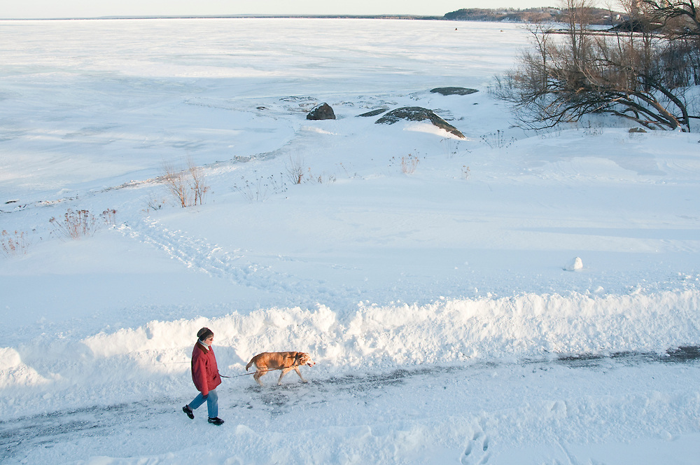 A woman walks her dog along the bike path in Marquette Michigan on Lake Superior in winter.