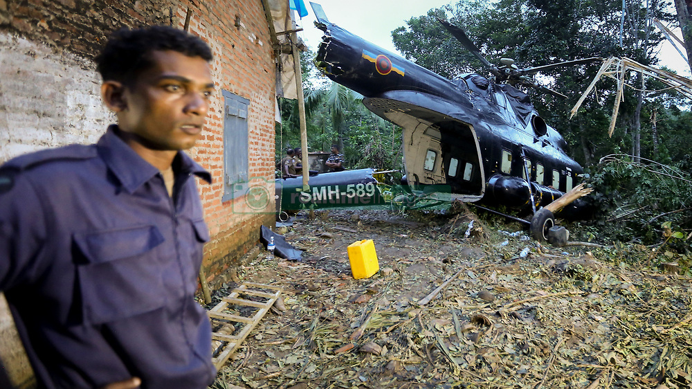 May 30, 2017 - Baddegama, Sri Lanka - A Sri Lankan Air Force soldier looks on beside the crash-landed  (SLAF) MI-17 helicopter that was carrying relief aid to flood victims in a flooded village, Baddegama, Galle District in the southern part of Sri Lanka on Tuesday 30 May 2017...A special investigation is now underway as to why the helicopter crash-landed. (Credit Image: © Tharaka Basnayaka/NurPhoto via ZUMA Press)