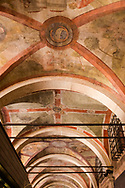 View of the faded painted scenes in an arched arcade over a street in Venice, Italy
