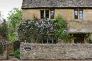 Traditional village property with climber and drystone wall in Broadway, The Cotswolds, Gloucestershire, UK