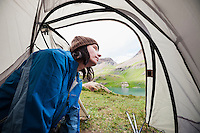 Female backpacker looks out tent at approaching thunderstorms at Ice Lakes Basin, San Juan mountains, Colorado, USA