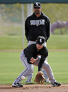 GLENDALE, AZ - FEBRUARY 24:  Manager Ozzie Guillen #13 watches Jayson Nix #5 of the Chicago White Sox field ground balls during a workout on February 24, 2010 at the White Sox training facility at Camelback Ranch in Glendale, Arizona. (Photo by Ron Vesely)